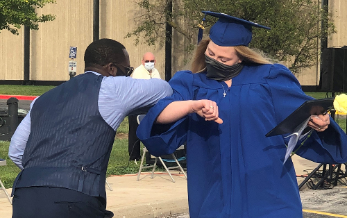 JVS Superintendent, Dr. Glenn Faircloth, gives a congratulatory elbow bump to Amber Stakes, at the JVS Adult Diploma Program Graduation Ceremony