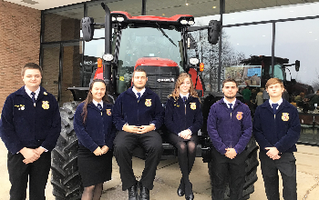 JVS FFA student members attend bruch with a farmer event and stand by tractor outside
