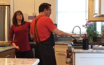 JVS Hospitality Services Instructor Maurina Driscoll films JVS Culinary Arts Instructor Chef Timothy Michitsch as he cooks at home for his JVS Facebook Culinary Group