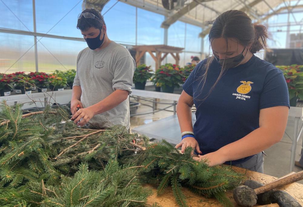 Elijah Caraballo (Columbia) and Cassandra Williams (Elyria), landscape and greenhouse management seniors trim pine trees for wreaths.