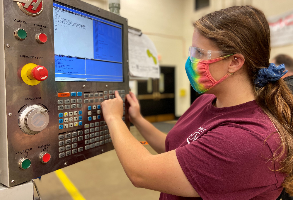 Female precision machine technology student works on CNC machine