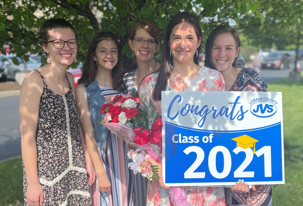 Four females smile with female grad student holding flowers and JVS grad sign