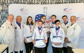 Lorain County JVS Culinary Arts students smile holding their awards alongside three ACF judges at the American Culinary Federation Competition
