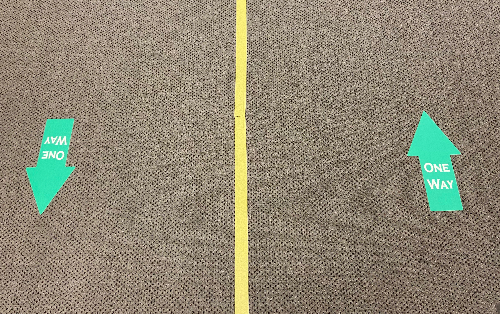 A hallway at JVS is clearly marked for one way traffic to assist with social distancing