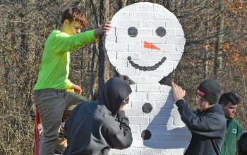 Masonry trades student position the snowman portion of their holiday lights display