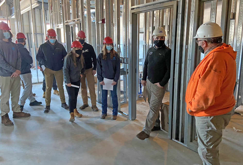 Industrial electricity students talk with electrial foreman on site at the new Oberlin Elementary school