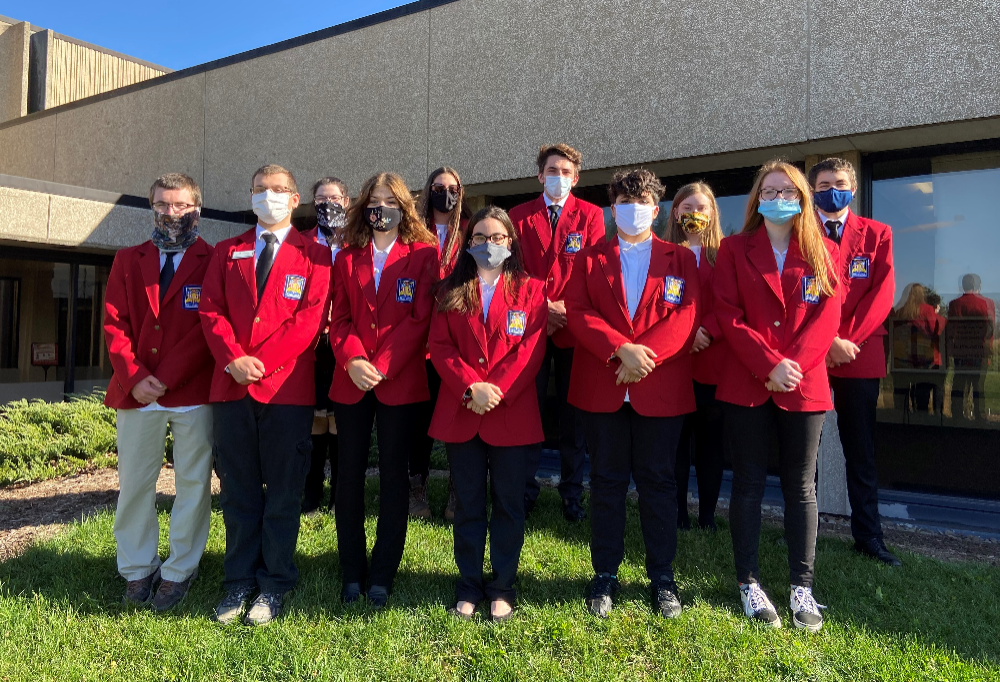 SkillsUSA team members stand outside on hill in red jackets