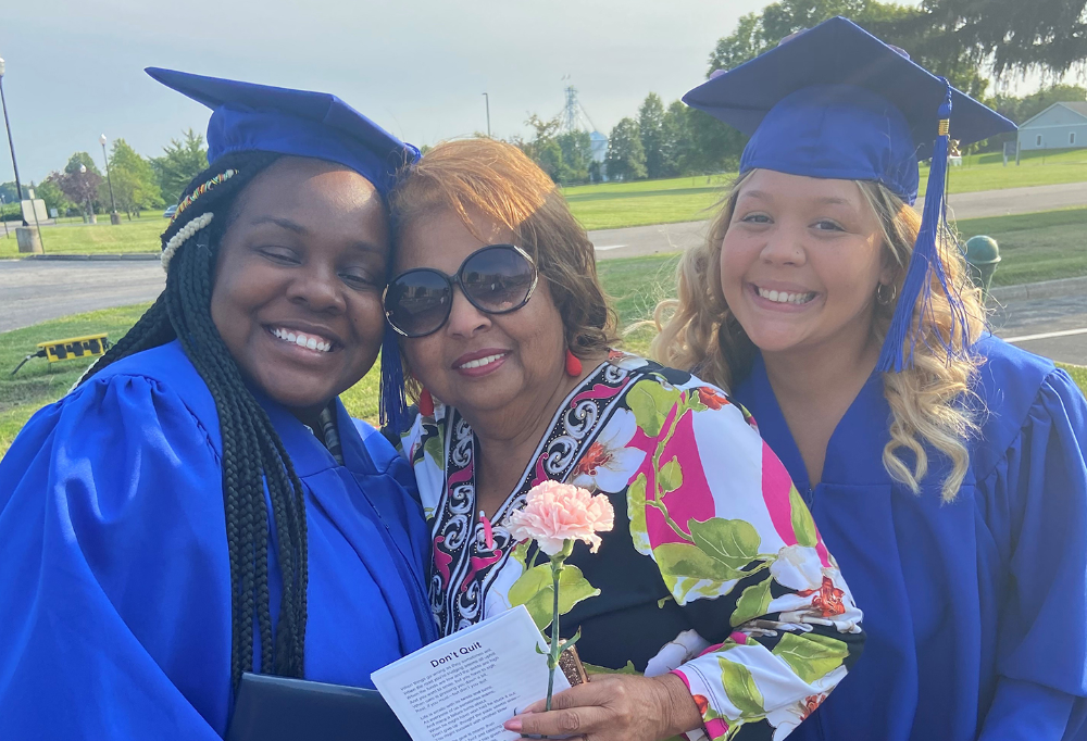 Two female grads smile in cap and gown with their LCJVS instructor