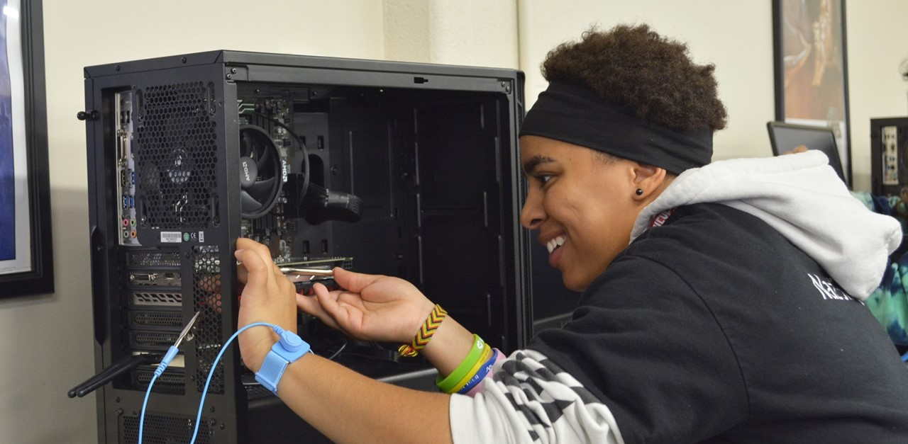 Female 9th grade student works in Network Communications Technology lab