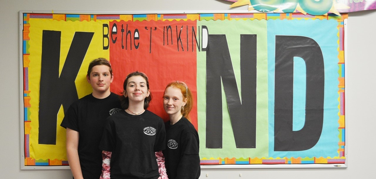 One male and two female students stand in front of bulletin board that reads Be the I in KIND