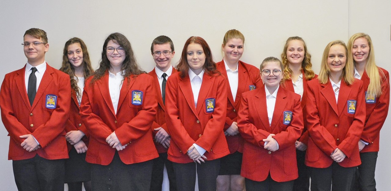10 high school students stand together in their red SkillsUSA jackets