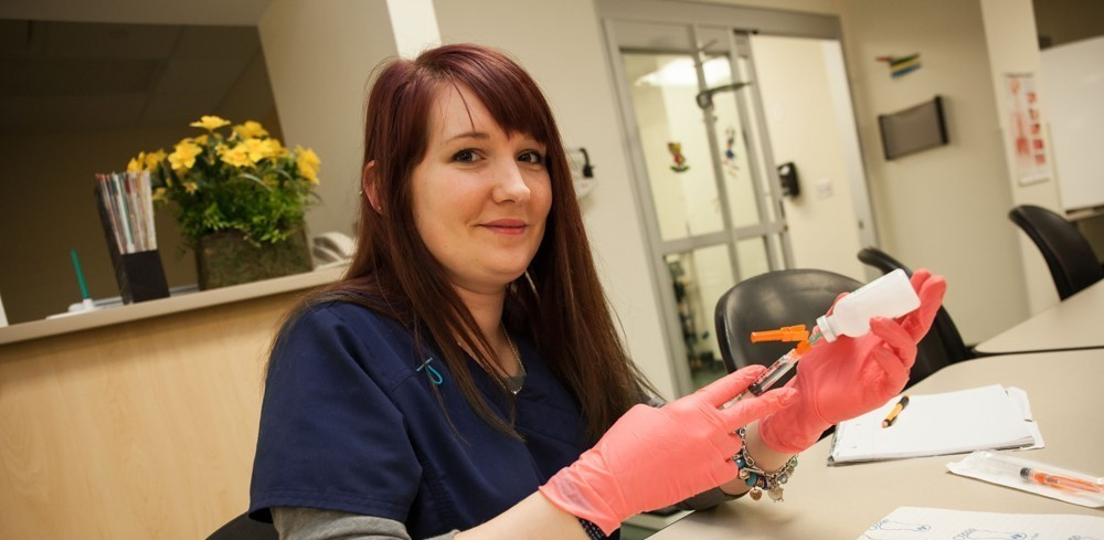 Female student practices drawing blood in her medical office lab