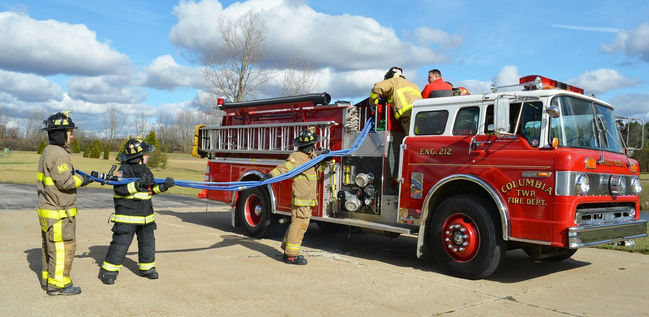 Public Safety seniors dressed in full fireman gear, load a triple layer hose in a firetruck outside