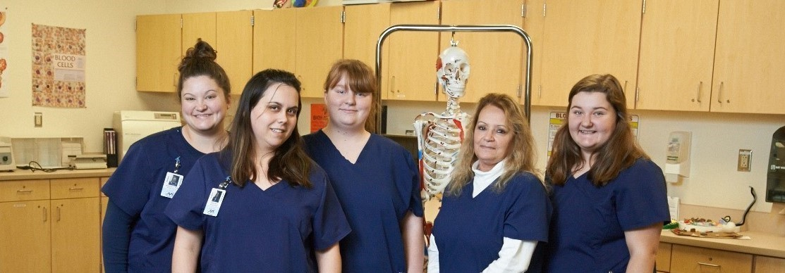 Five female students smile in the medical assisting lab with a skeleton