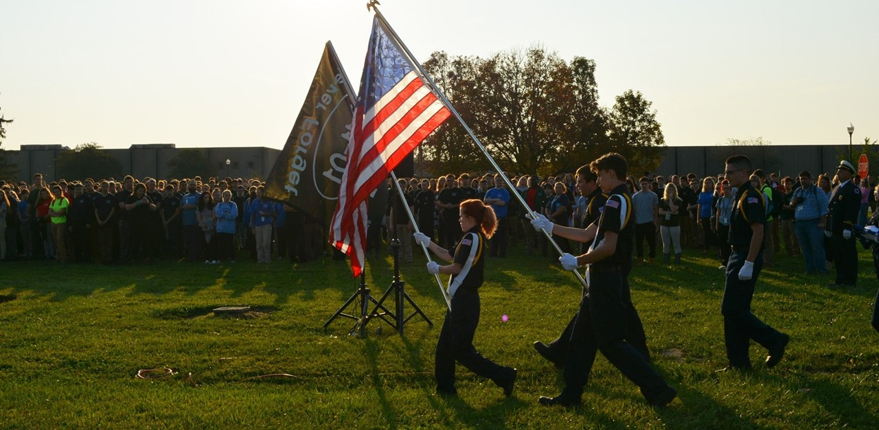 JVS staff and students attend Patriot Day ceremony - students carry American flag