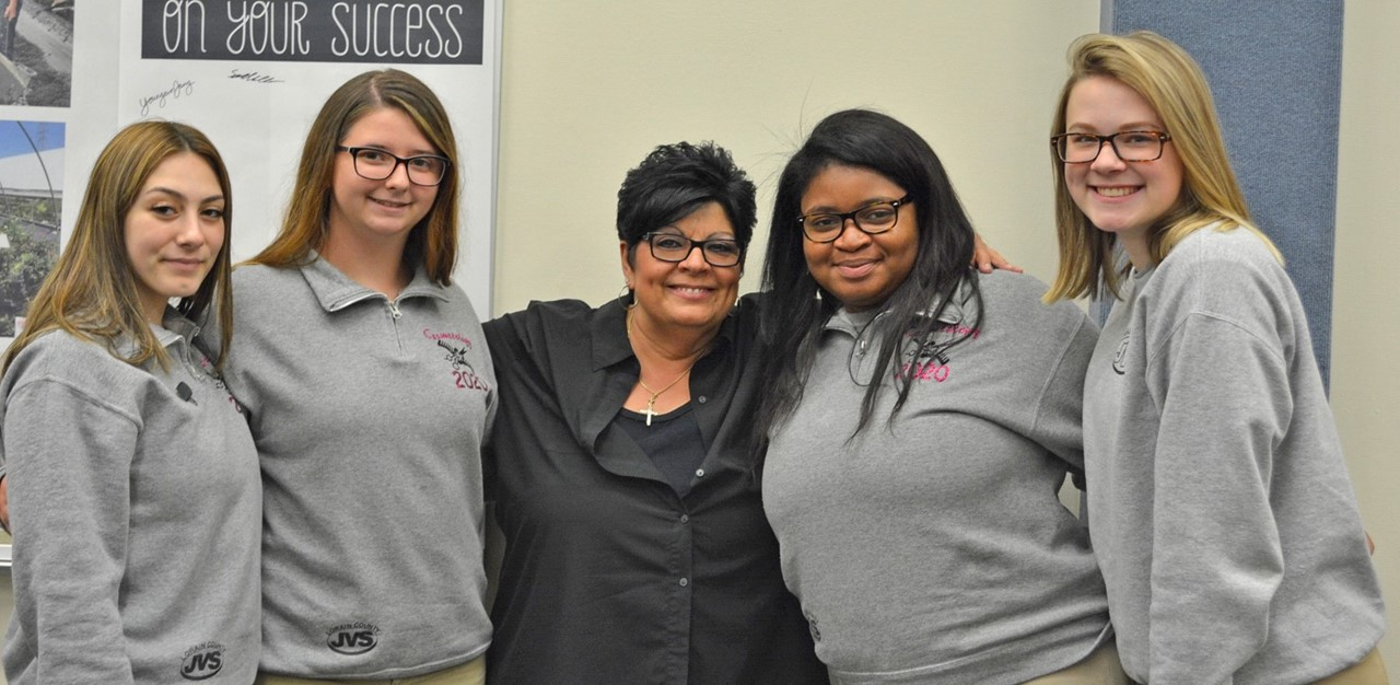 Four female costmetology  student smile with instructor