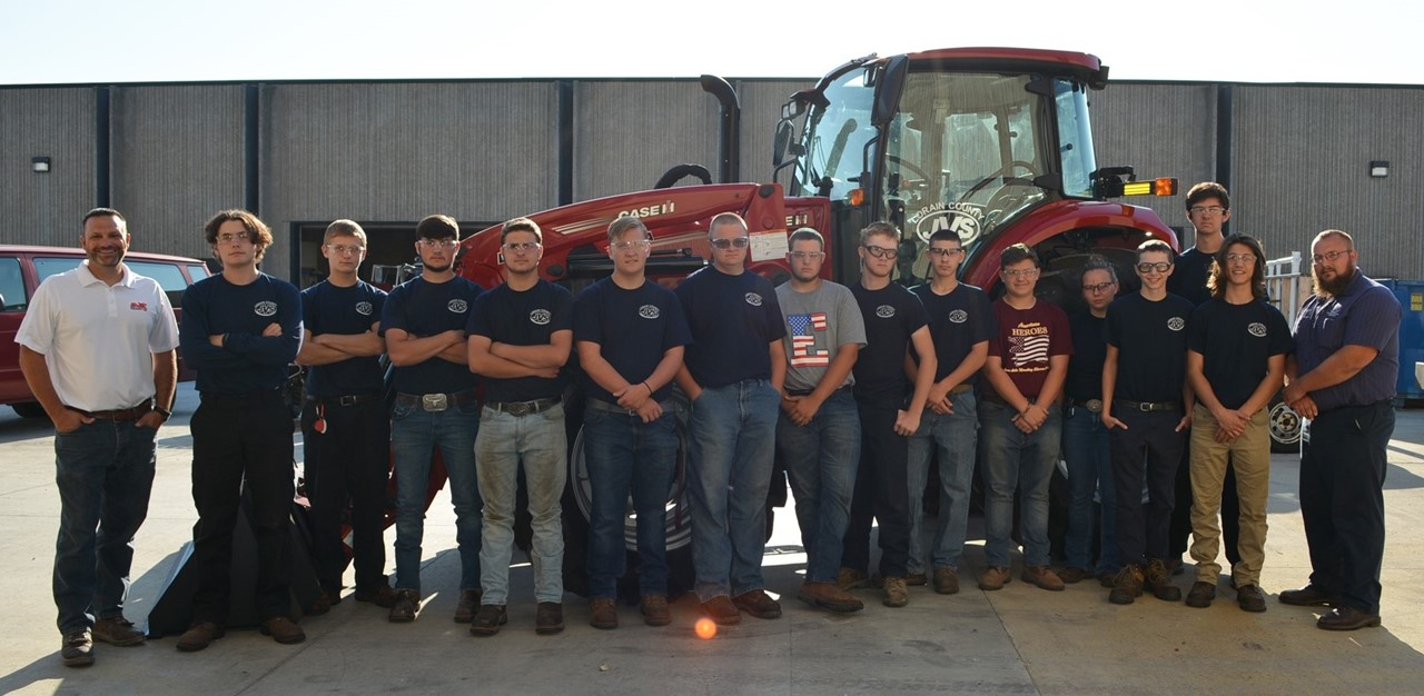 Industrial Equipment Mechanic students stand in front of Case IH tractor with Wellington Implement GM