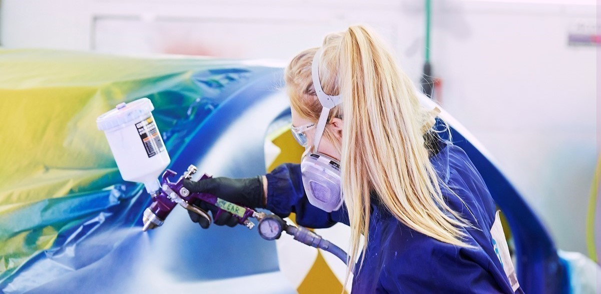 Female student in the collision repair program spray paints a car
