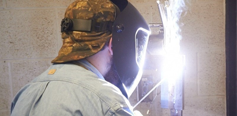 Male student welds in lab