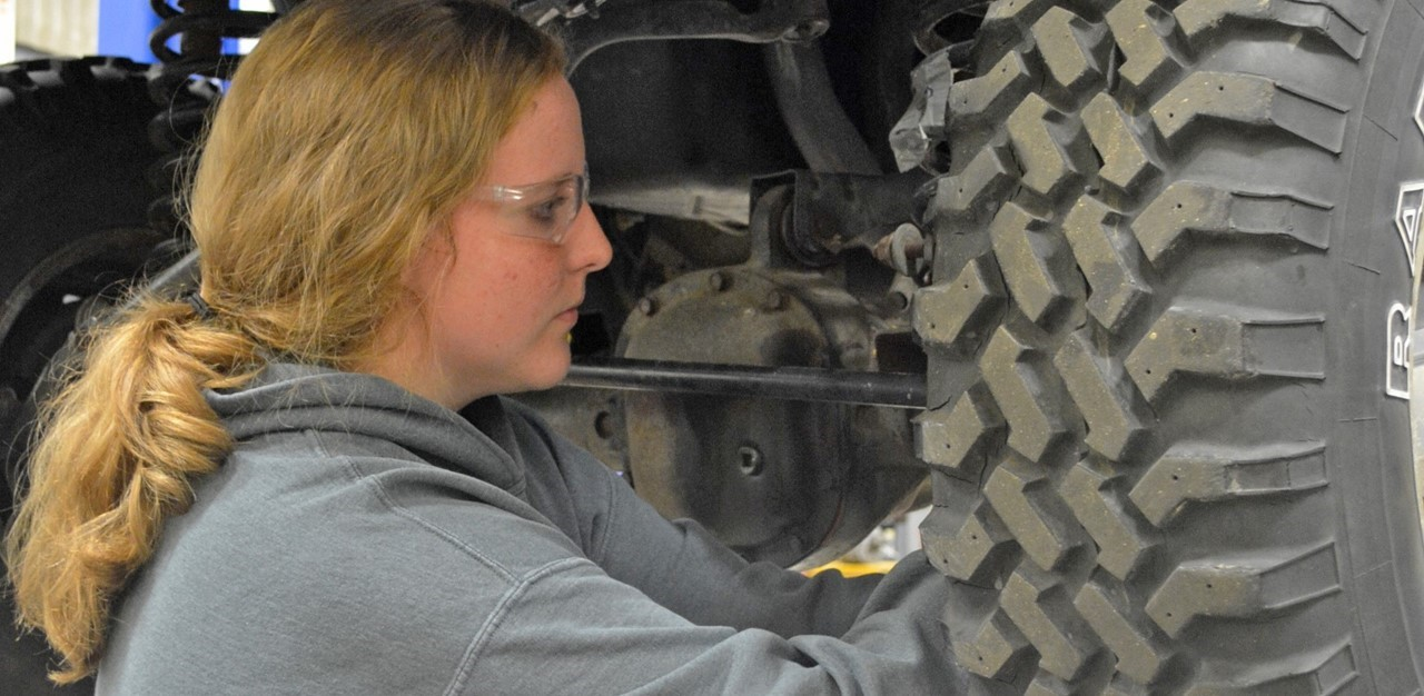Female student works on brakes of a car in lab