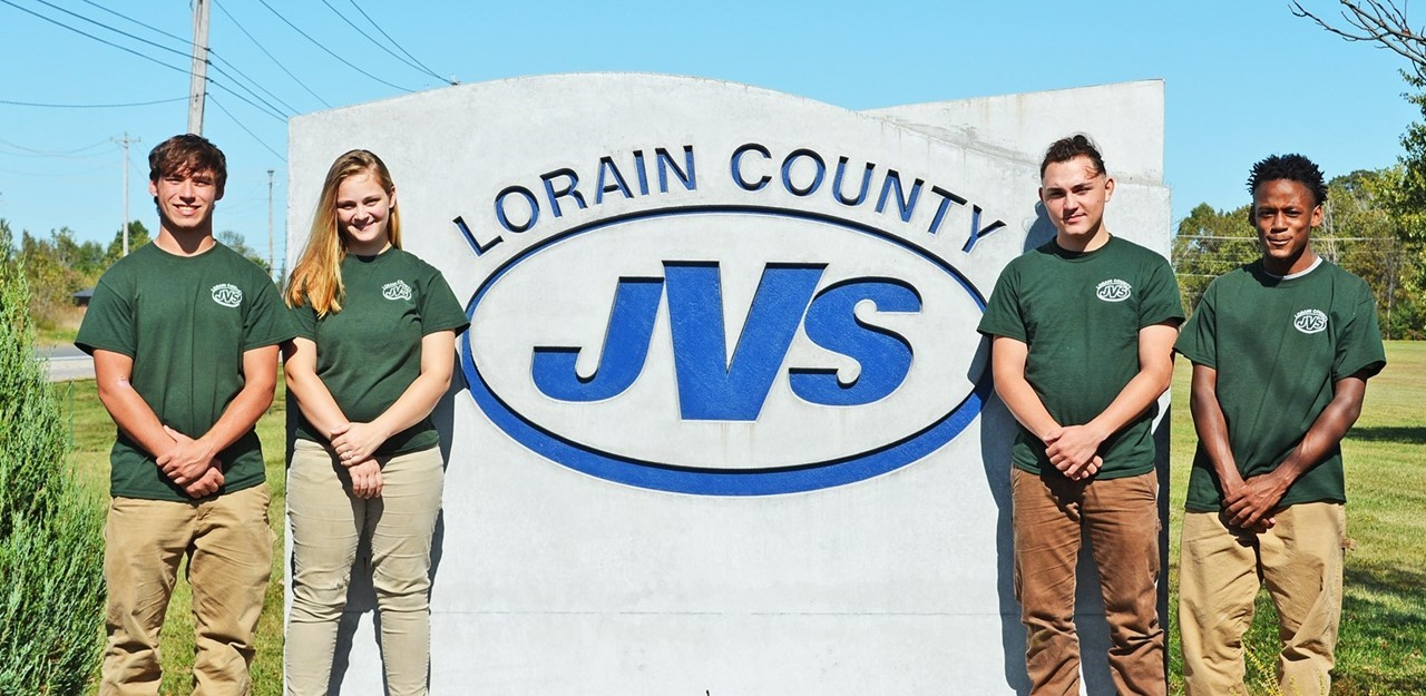 Four high school students stand outside in front of JVS logo sign