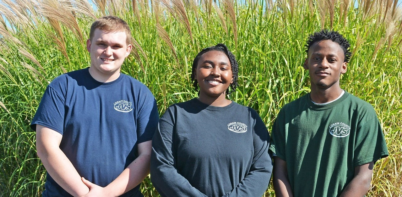 Three high school students stand outside in front of large tall grass