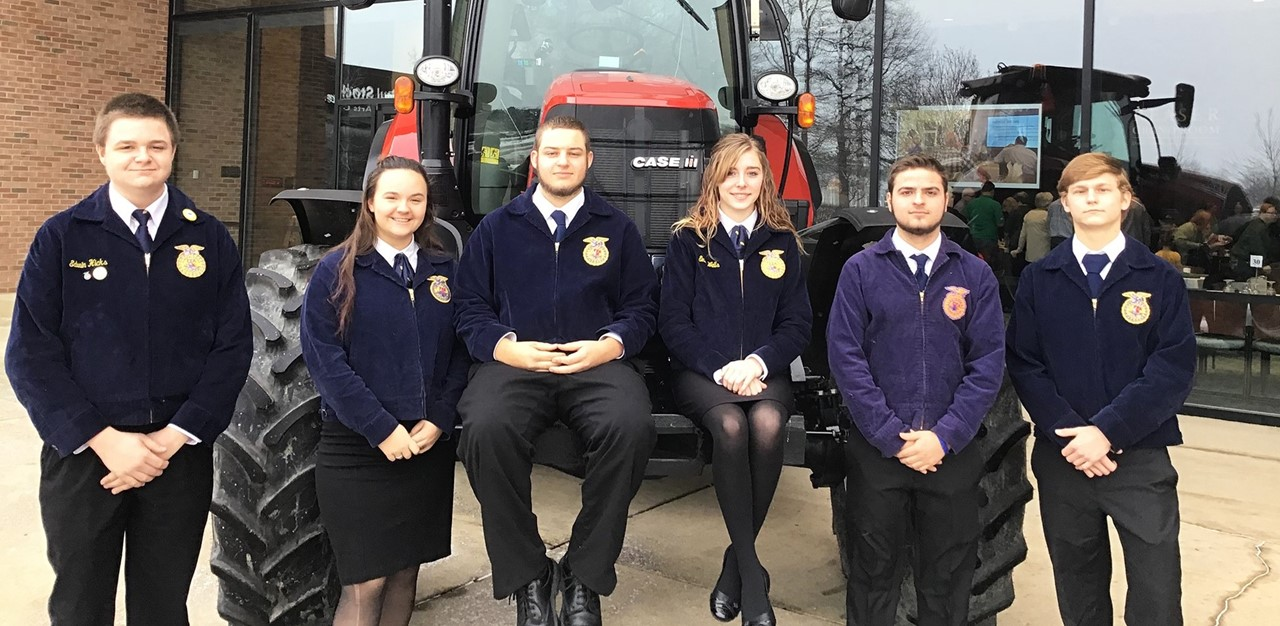 FFA Chapter student stand outside near a tractor at Brunch with a Farmer event