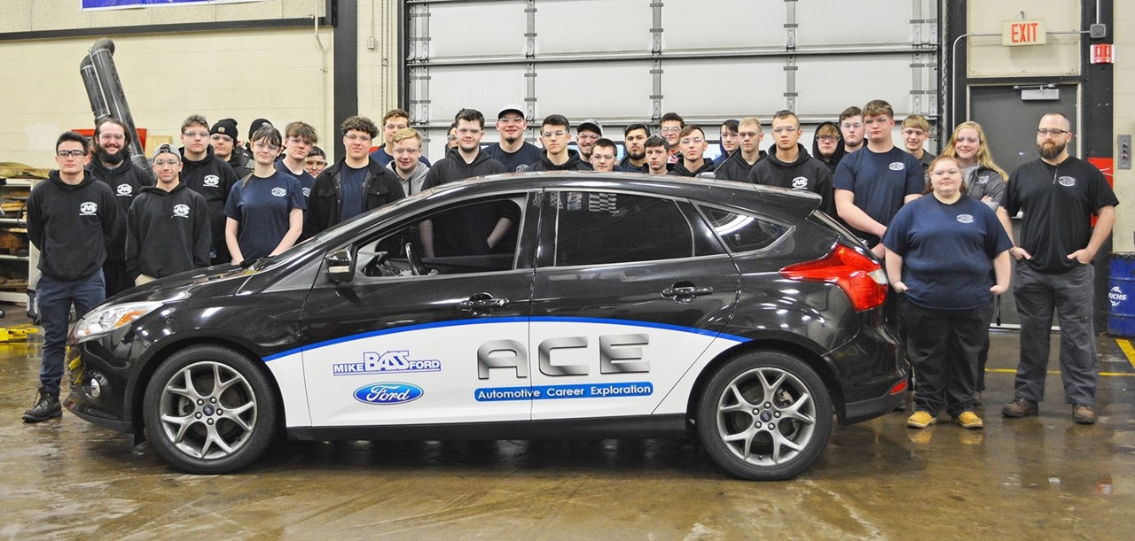 Auto technology junior and senior students stand by the ACE program car with their instructor Eric Hohoman in their lab