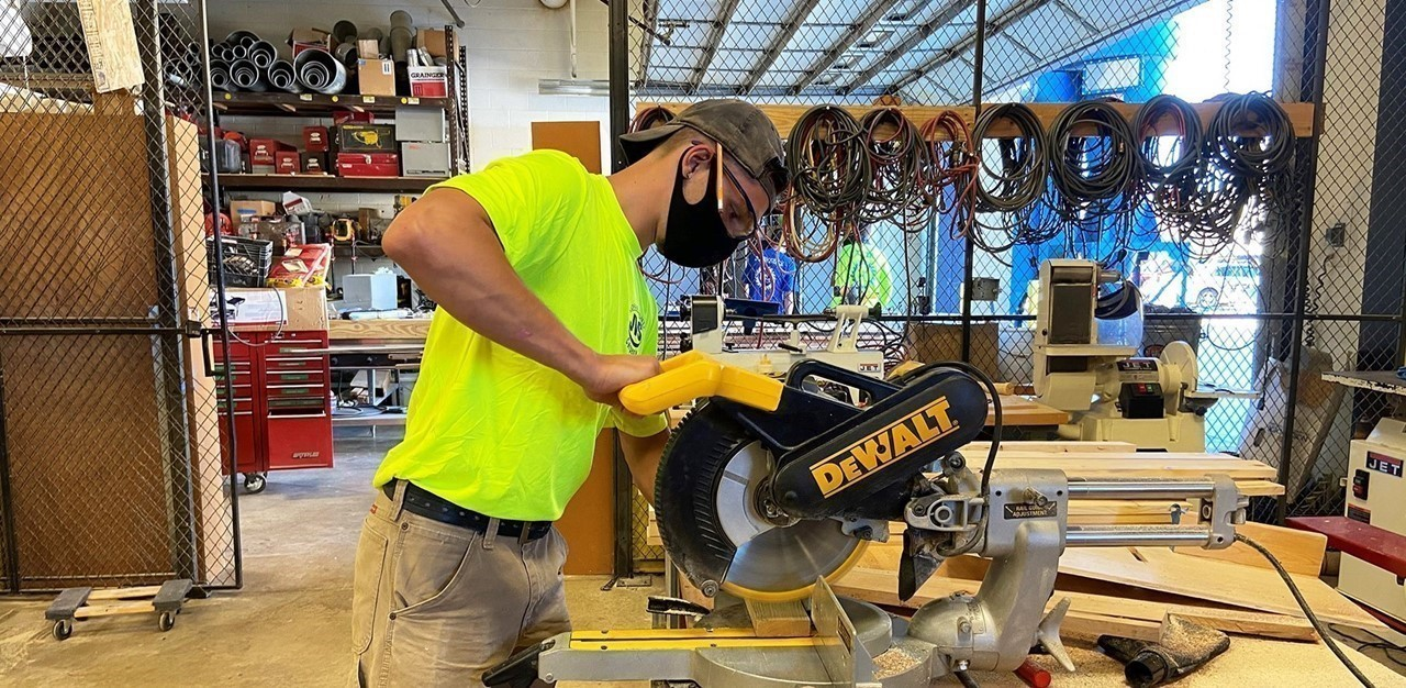 Male carpentry student, wearing a mask, using a hand saw in his career tech lab