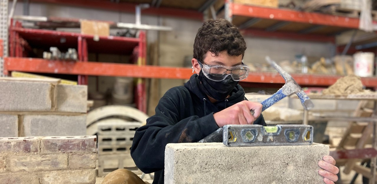 Male student lays block and uses a hammer in the masonry trades lab