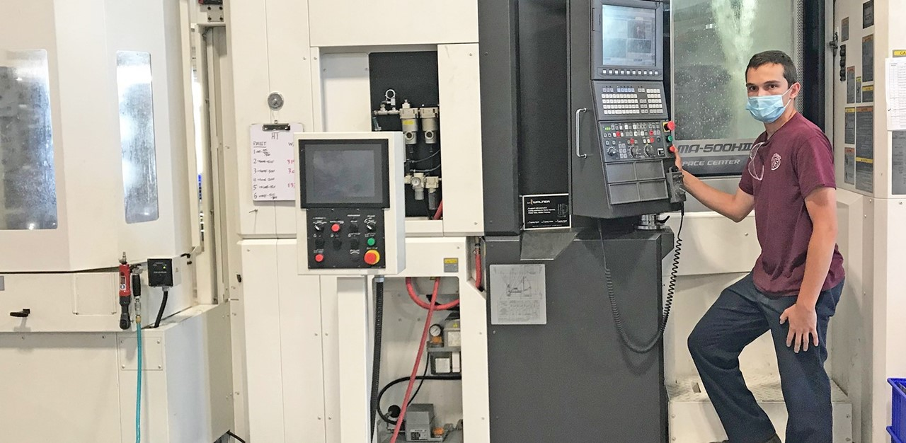 Male student stands in front of large CNC machine with mask on