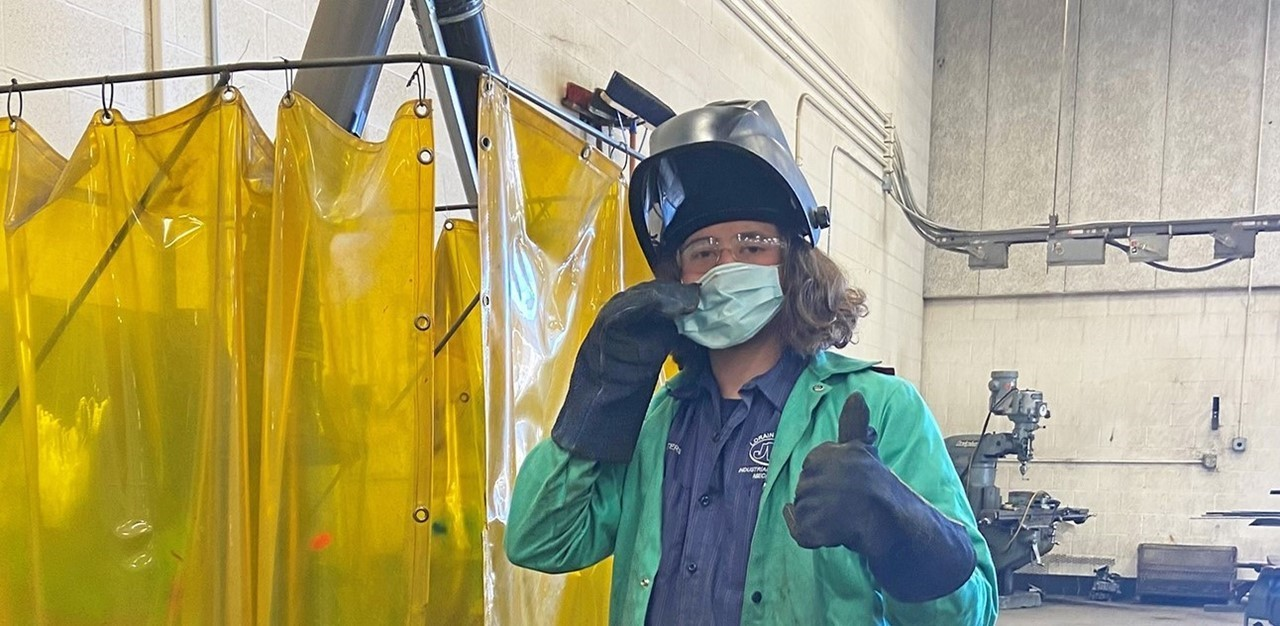 Male student in welding gear and mask gives a thumbs up