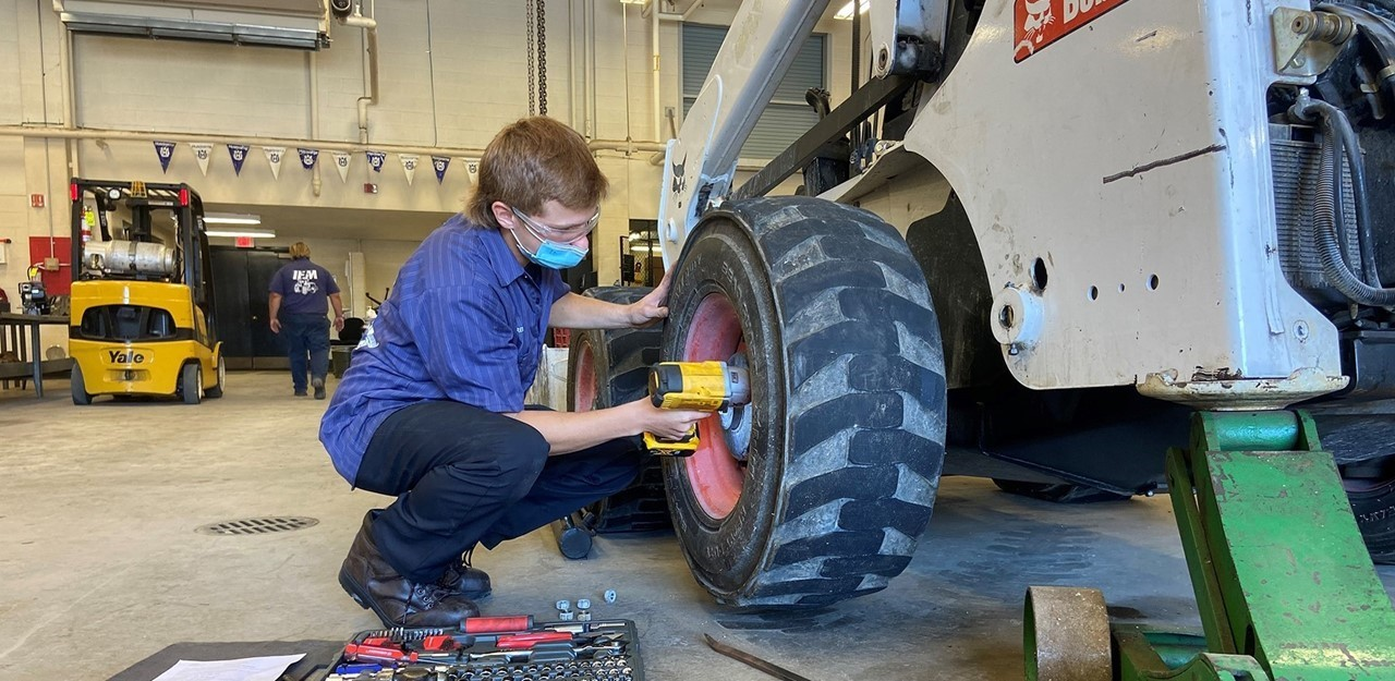 Male student, wearing a mask, works on a bobcat in his career tech lab