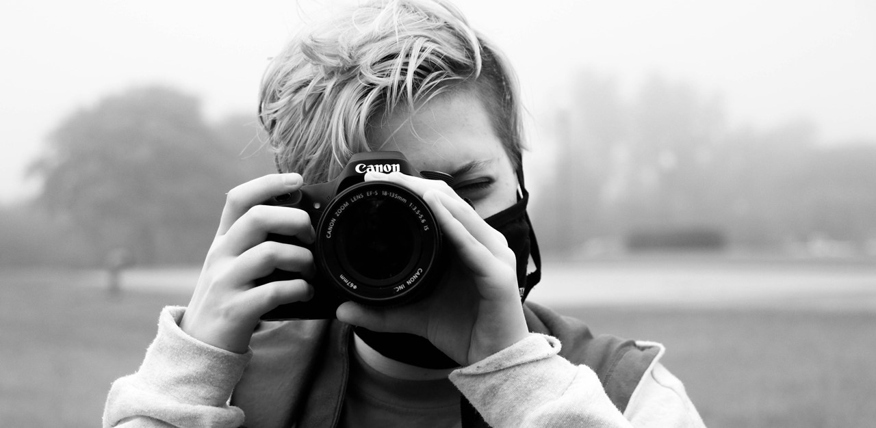 Black and white photo of female holding a camera up to her face ready to take a picture